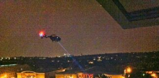 helicopter with spotlight over riot scene