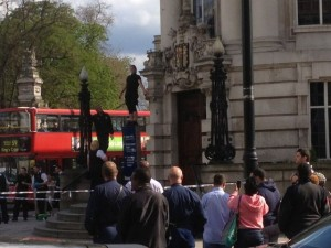 The man was balanced on top of a sign. His face has been obscured by Brixton Blog