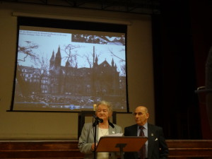 Ann Kirk relates her memory of Berlin after Kristallnacht beneath the image of a destroyed synagogue.