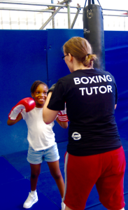 Dwaynamics boxing coach helping a schoolgirl to practice jabs and crosses (Photo: Brixton Blog)