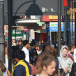 Crowds of people walk down Brixton Road in the sunshine