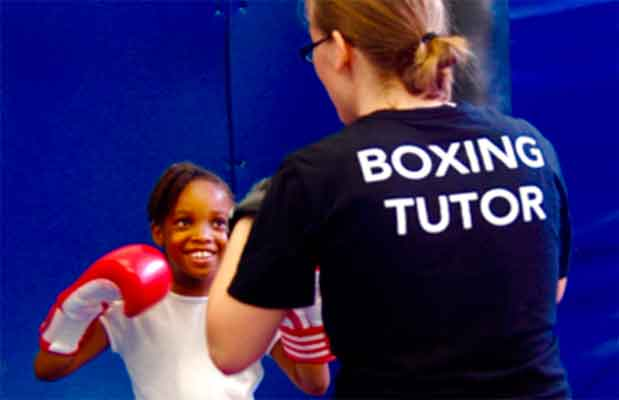 Dwaynamics boxing coach helping a schoolgirl to practice jabs and crosses