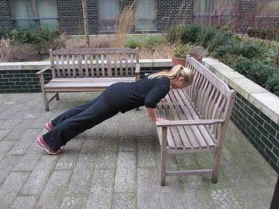 woman doing press ups on a bench