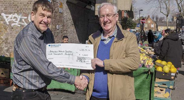 Fred Taggart (right) receives a £1,000 donation for the Brixton Advice Centre from Stuart Horwood of the Brixton Market Traders Federation