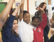 Kids at Baytree with hands raised and smiling