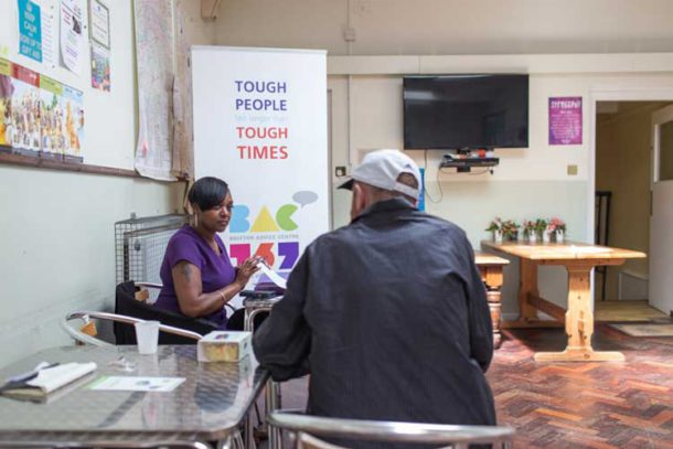 Adviser Sue Noel helps a visitor to the Brixton food bank. Photo by James Hopkirk