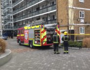 Fire crew stand next to burnt Effra Road flat