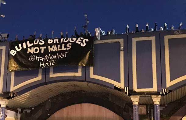 Advocacy Students unfurl banner at Brixton Rail Station saying Build Bridges not Walls