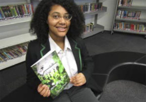 Student Micah with her book which tops Amazon best seller list