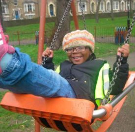 Child on swing at Max Roach Park