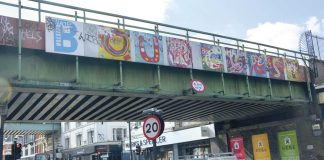 Bridge over Brixton Road with BE OUR Guest slogan