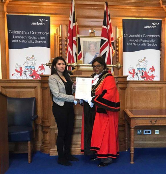 Maureen Madrid (left) receiving her citizenship certificate from Lambeth mayor Marcia Cameron