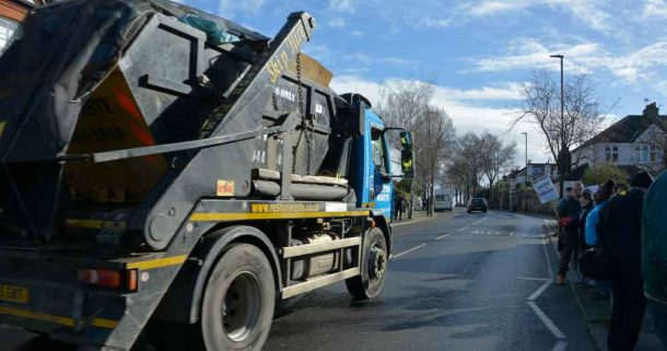 A lorry carries waste away past protesters outside the Carnegie building