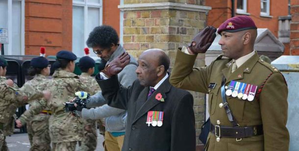 Neil Flanigan takes the salute with Lieutenant Colonel Sulle Alhaji at last year's Remembrance Day ceremony in Windrush Square