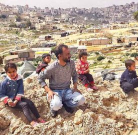 A family sit at the site of their demolished home in Jabal Al Baba