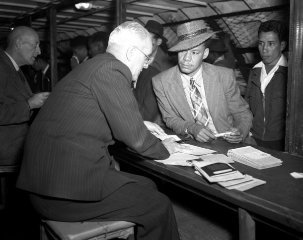 Photo shows straw hatted Jamaican Leslie Wight telling Ministry of Labour his qualifications in the Labour Exchange 120 feet below ground.<br /> 23 June 1948