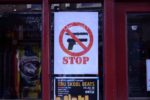 Stop knife gun sign in Brixton shop window