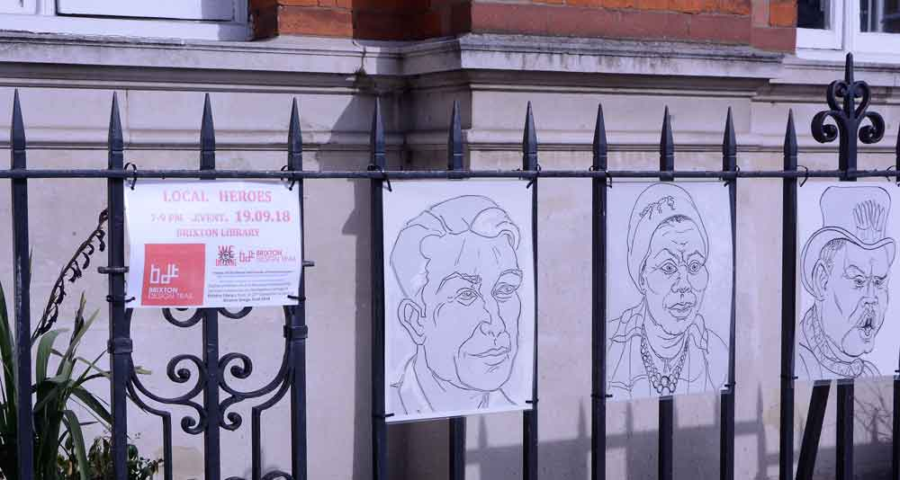 Brixton local heroes portraits hung on railings of Brixton Library