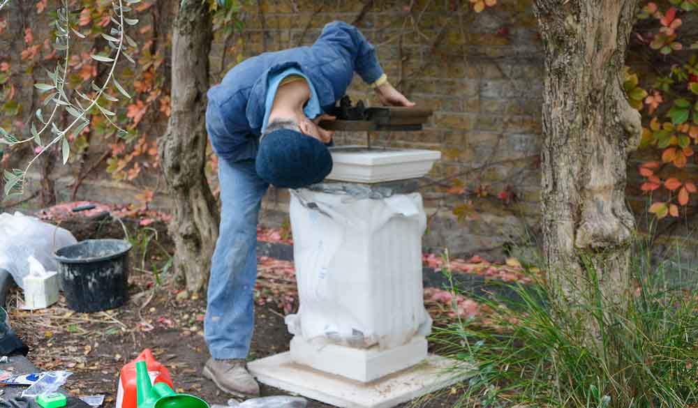 Anthony Padgett places the base for the bust which carries a sunflower and the pipe from van Gogh's famous Chair painting