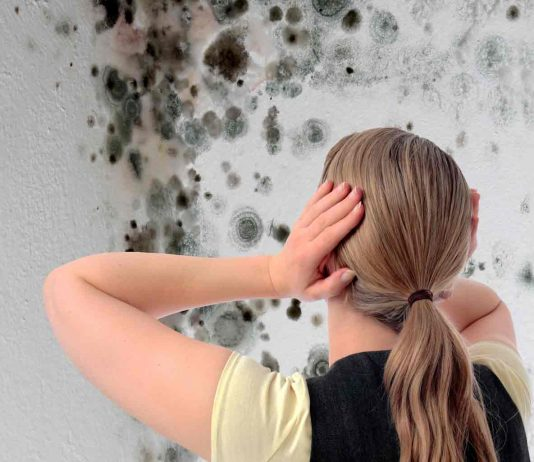 Woman looking at damp on wall