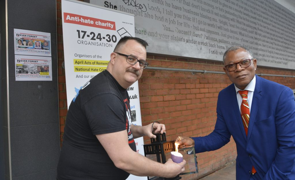 Mark Healey of HCAW and local councillor Donatus Anyanwu, representing the mayor of Lambeth, light one if the three candles