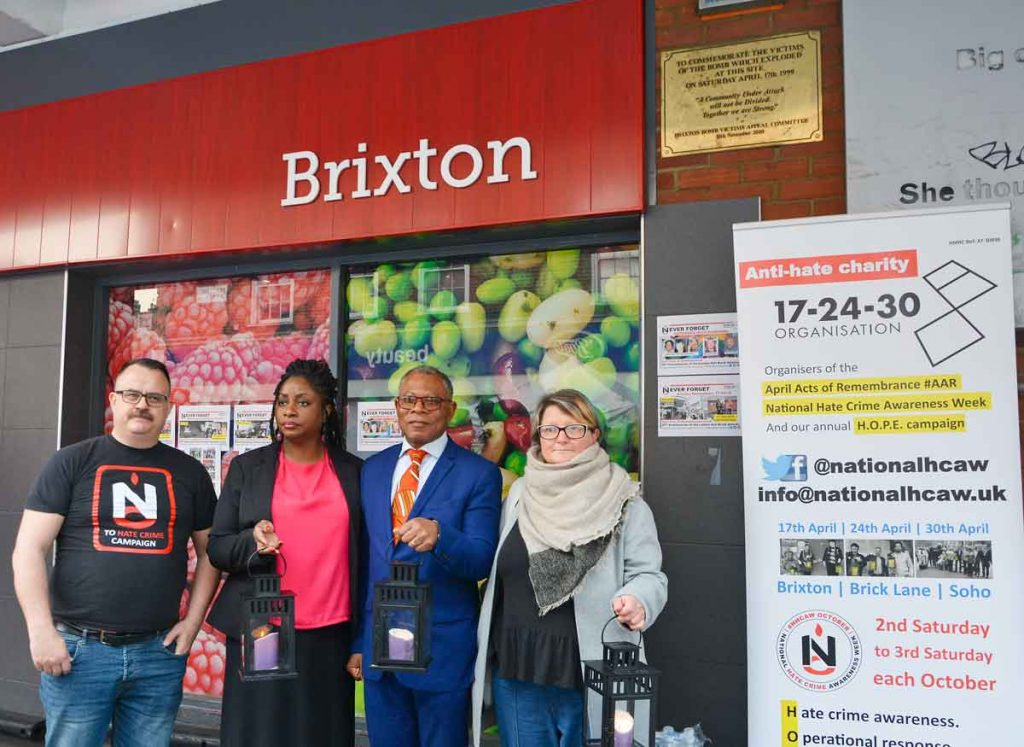 In front of the plaque on the side of Iceland that marks the sport where the bomb was left: Mark Healey of HCAW; Chery Lewis; Donatus Anyanwu; and Louise Holden, London disability hate crime project manager for Inclusion London, an organisation that supports more than 70 deaf and disabled organisations in every London borough