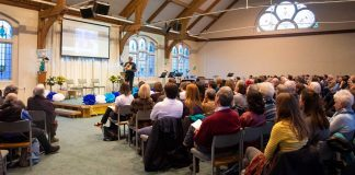 Crowd gathered in Herne Hill church hall to welcome refugee family
