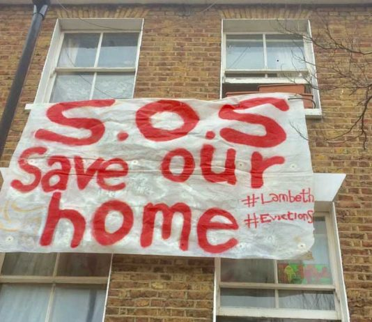 banner hung out of window of house where occupant threatened with eviction