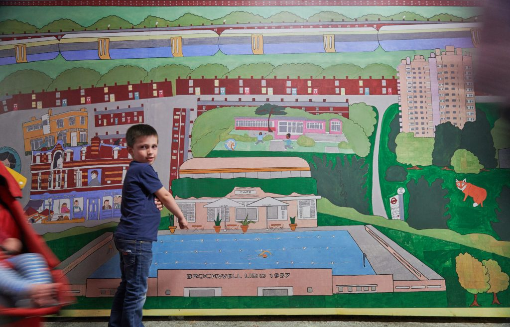 child standing in front of mural
