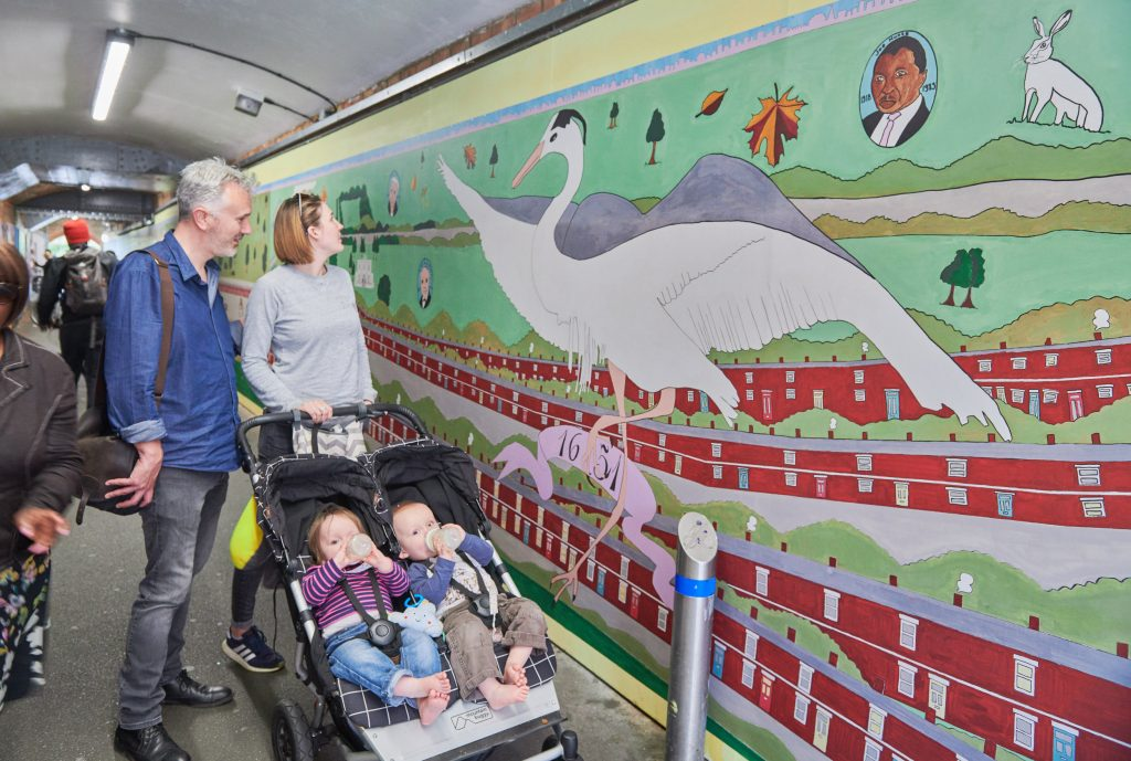 parents and children observing mural