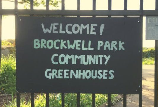 sign reading welcome to brockwell park community greenhouses