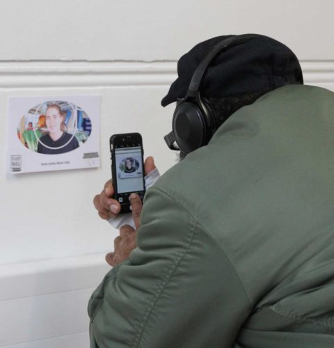 Visitor scans an oral history card to hear stories that explain the pictures on the wall
