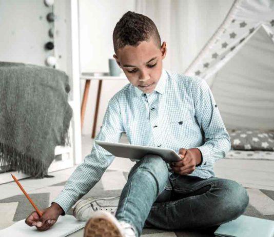 boy doing homework on laptop