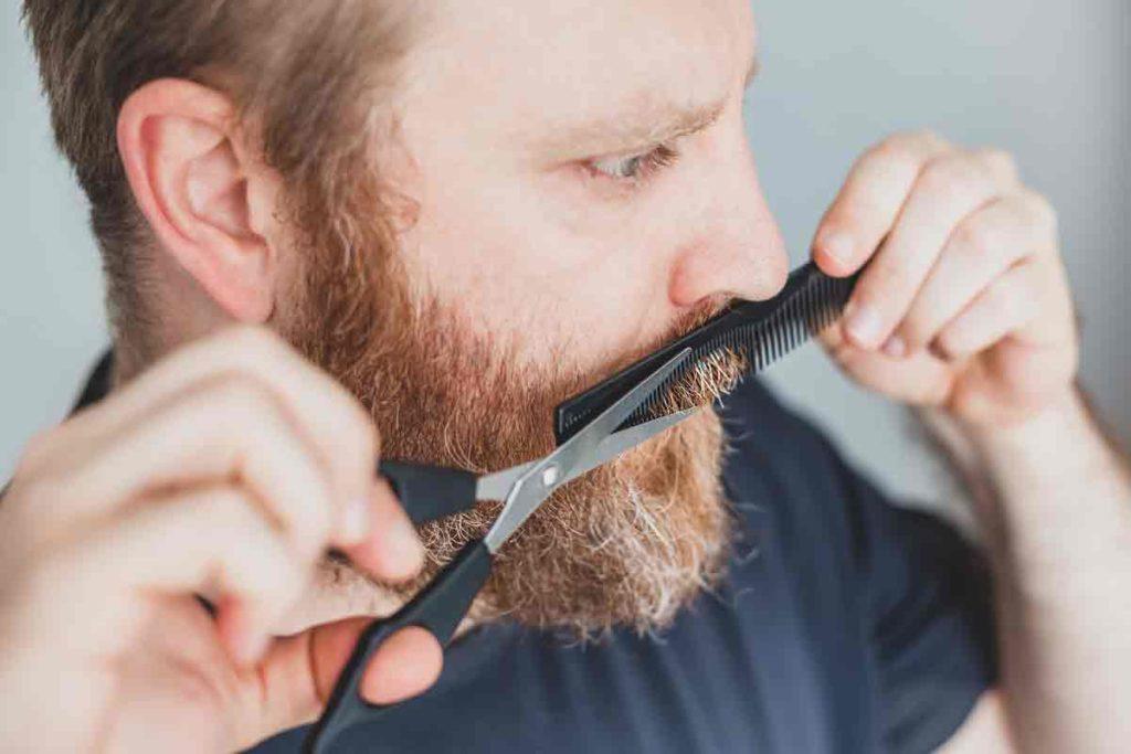 man trimming moustache