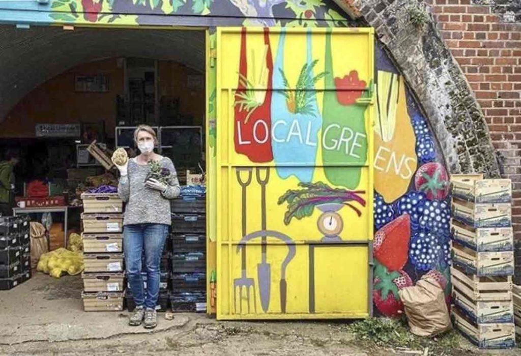woman in front of doors of vegetable store