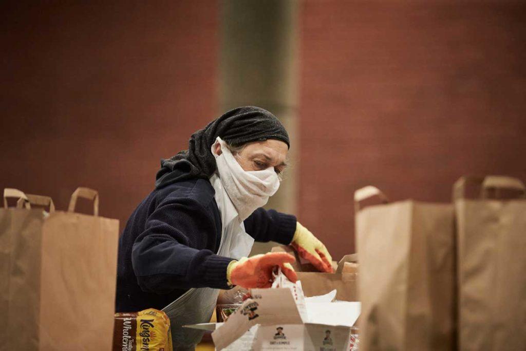 Women wearing mask packing foodbank parcels