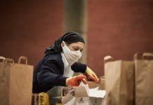 Woman wearing mask packing foodbank parcels