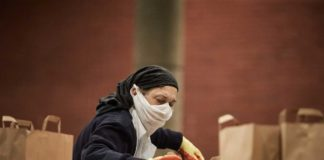 Women wearing mask packing foodbank parcels