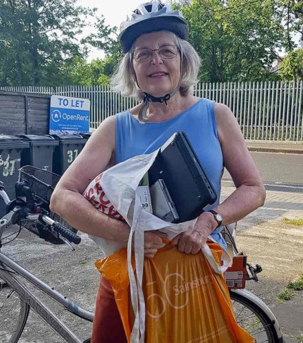 woman with used laptop and bicycle