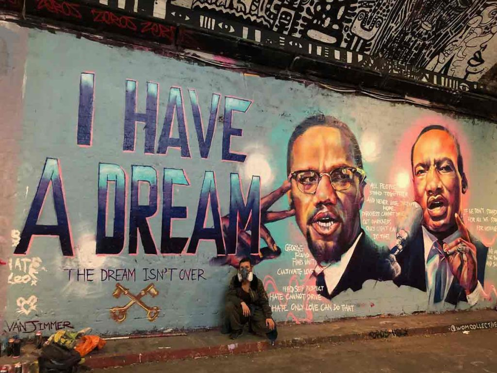 graffiti artist with images of MLK and Malcolm X
