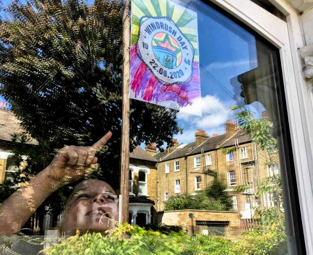 child looks at Windrush poster in window