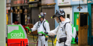 Workers in protective clothing spraying objects