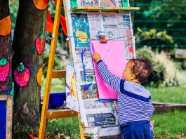 young girl drawing on easel
