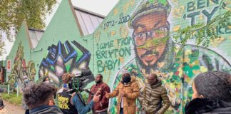filming in front of mural