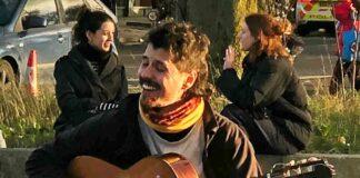 man playing guitar in street