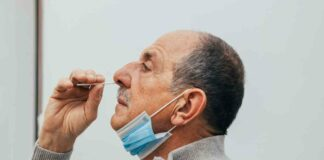 man putting swab in nose