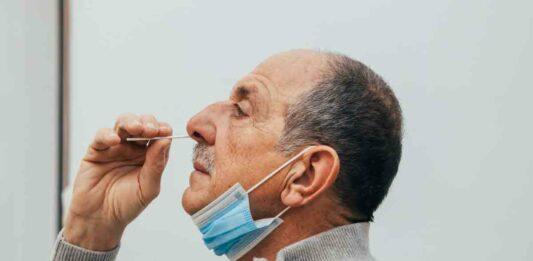 man putting swab in nose