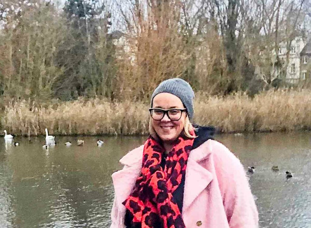 woman in front of pond with swans