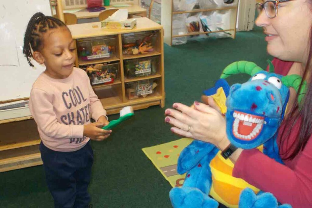 child with giant toothbrush in nursery