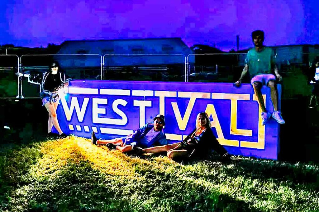 festival-goers in front of a sign
